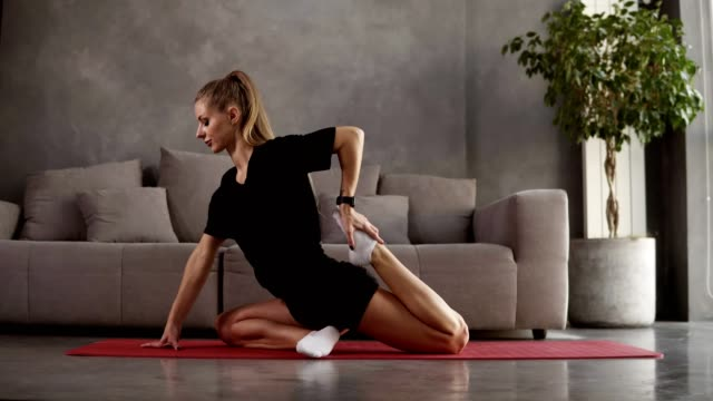 Flexible woman practice yoga postures and doing stretching in loft interior room, slim girl doing stretching exercise on mat. Female pilates body care concept. Healthy and sport lifestyle video