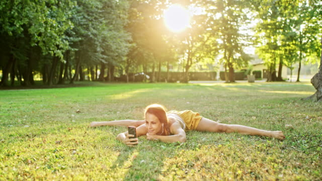 Video MS Flexible young woman practicing splits, using smart phone in grass in sunny park