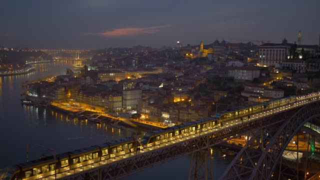 Flexity Outlook Eurotram trains of the Porto Metro meets on Dom Luis I Bridge. Night shot after sunset of Porto, Portugal video