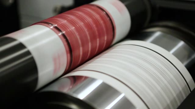 flexography printing process on in-line press machine. video of photopolymer plate stuck on printing cylinder, substrate is sandwiched between the plate and the impression cylinder to transfer the ink - литография стоковые видео и кадры b-roll