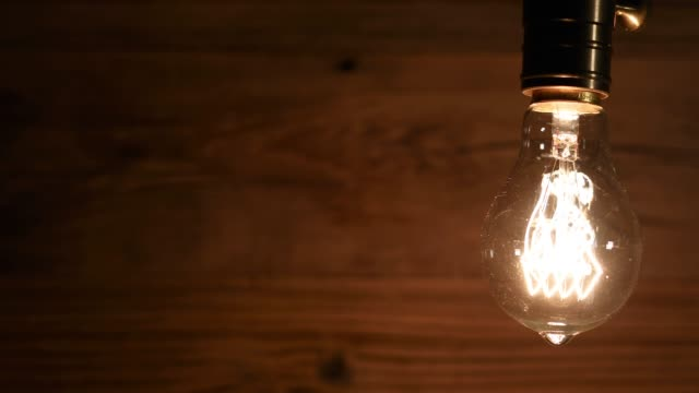 flickering light bulb against a wooden background