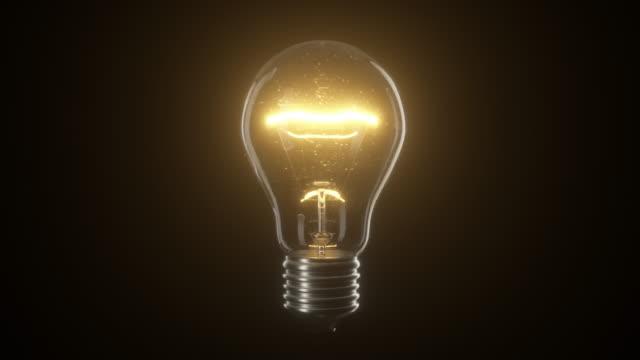 vídeos de stock, filmes e b-roll de lâmpada de cintilação do bulbo de luz do tungstênio sobre o fundo isolado preto - lampada