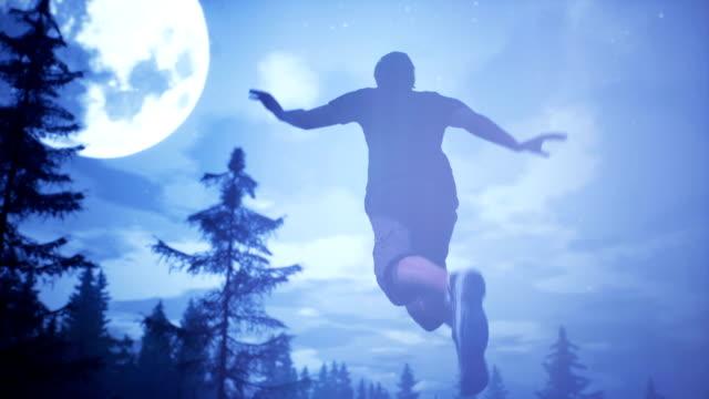 ufo flyger över skogen och fångade man i ljusstrålen. dramatiska super realistisk koncept. - rymdvarelse bildbanksvideor och videomaterial från bakom kulisserna