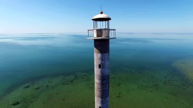 stockvideo's en b-roll-footage met 4 k. vlucht en opstijgen over de oude vuurtoren staande in de zee, luchtfoto. estland, saaremaa island, kiipsaare tuletorn. - estland