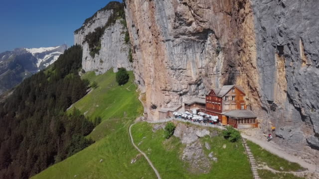 Flight around chalet in the rock on Ebenalp, Canton of Appenzell, Switzerland Aerial view of chalet on Ebenalp, Switzerland chalet stock videos & royalty-free footage