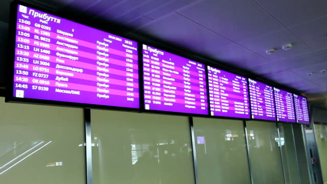 Flight arrivals and departures info screens on monitor in airport video