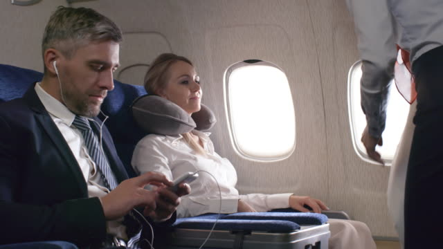 Flight Attendant Giving Blanket to Passenger PAN shot of female flight attendant closing window shade and giving blanket to cheerful woman with travel pillow. Businessman in earphones sitting in aisle seat and listening to music blanket stock videos & royalty-free footage