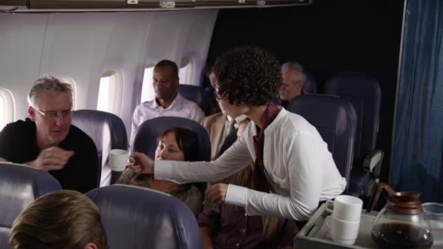 flight attendant serving drinks to airliner passengers - kabina filmów i materiałów b-roll