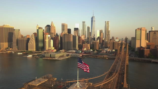 AERIAL: Flight backwards over Brooklyn Bridge with Manhattan view close up of American Flag at Sunrise/Sunset (4K)