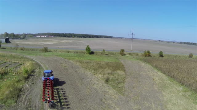 Flight behind  agricultural tractor in field. Aerial video