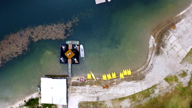 büyük bir gölün kayalık bir kıyısında uçuş - sale stok videoları ve detay görüntü çekimi