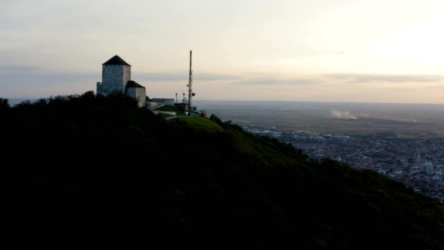 arka planda gün batımı ufku olan bir tepenin tepesindeki kulenin yakınında uçuş - sale stok videoları ve detay görüntü çekimi