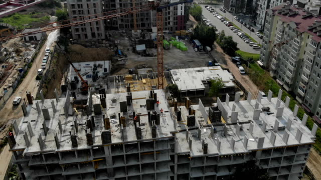 Flight near the unfinished monolithic house. Construction crane near the construction site. Top view of the construction