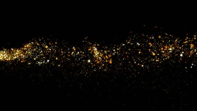 vídeos de stock, filmes e b-roll de vôo de uma estrela luminosa e dispersão de partículas redondas de ouro em um fundo preto 4k - incandescência