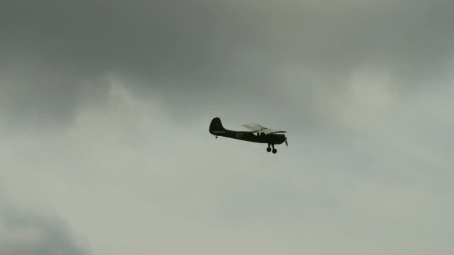 Flight of retro plane Retro airplane flying in cloudy sky propeller airplane stock videos & royalty-free footage