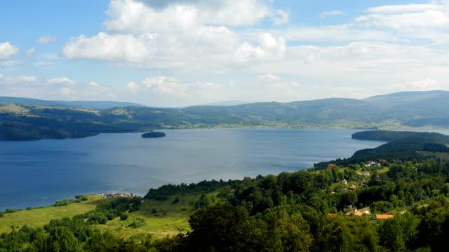 bulutlu bir günde güzel bir dağ gölünün sahili üzerinde uçuş - sale stok videoları ve detay görüntü çekimi