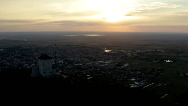 Flight over a hill with a town under it and a scenic sunset panorama