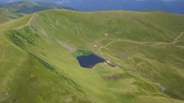 Flight over a mountain lake. Incredible landscape of green mountains in late summer. Lake Vorozheska in Carpathian mountains, Ukraine. video
