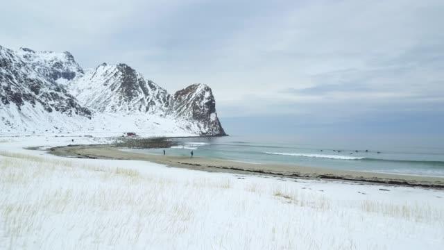 vídeos de stock e filmes b-roll de flight over a snowy beach towards a blue wavy ocean in lofoten, norway. - lofoten