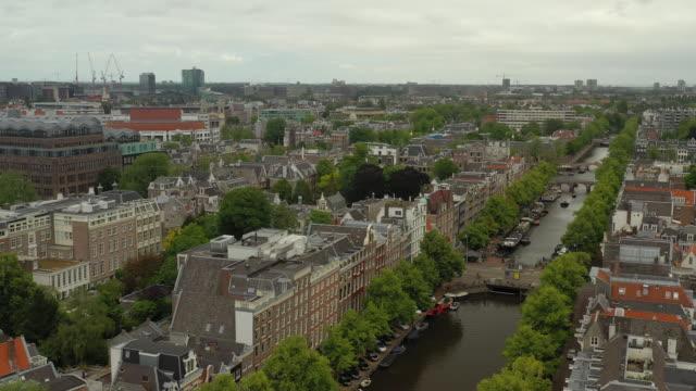 flyg över amsterdam stadsbild molnigt dag canal aerial panorama 4k nederländerna - drone amsterdam bildbanksvideor och videomaterial från bakom kulisserna