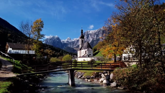 Flight over bridge near famous Parish church St. Sebastian, in Ramsau, Berchtesgaden, Bavarian Alps, Germany.