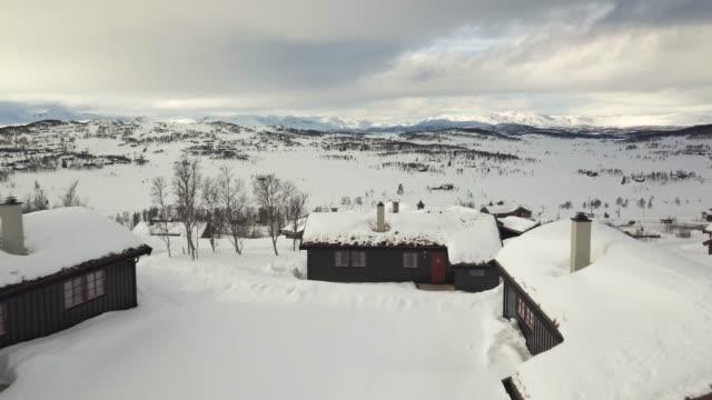 flug über hütten in norwegen an einem bewölkten wintertag. - blockhütte stock-videos und b-roll-filmmaterial