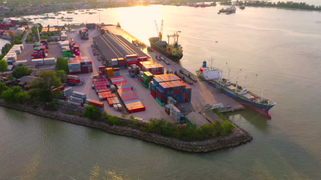 vídeos de stock e filmes b-roll de flight over cargo ship at sunset in industrial port in thailand with many container vessel ship and big crane working - drone shipyard night