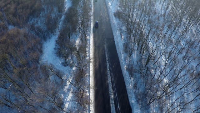 Flight over Cars riding on road in winter forest, AERIAL video