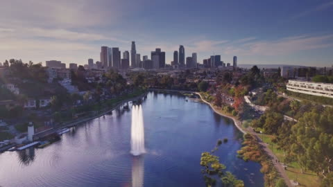 Flight Over Echo Park, Los Angeles Drone shot of Echo Park Lake, a reservoir in Los Angeles surrounded by a public park. The neighborhood of the same name is now one of the city's trendiest. The DTLA skyline is in the distance. drone point of view stock videos & royalty-free footage