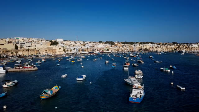 Flight over harbour with traditional fishing boats in fishing village Marsaxlokk, Malta Aerial view of Marsaxlokk harbour, Malta malta stock videos & royalty-free footage
