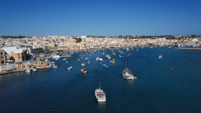 Flight over harbour with traditional fishing boats in fishing village Marsaxlokk, Malta