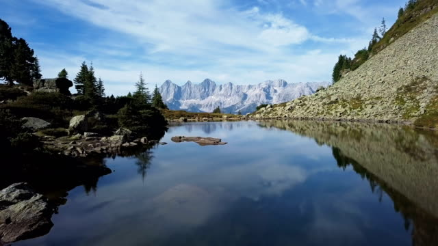 stockvideo's en b-roll-footage met vlucht over lake spiegelsee (mirror lake) met reflecties van de dachstein-bergen. reiteralm, schladming-dachstein, oostenrijk. - alpen