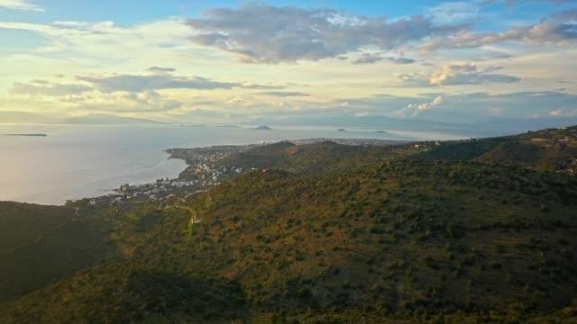 vídeos de stock, filmes e b-roll de voo sobre montanhas da ilha de aegina para cidade de egina, grécia em belo pôr do sol com céu dramático. - ática ática