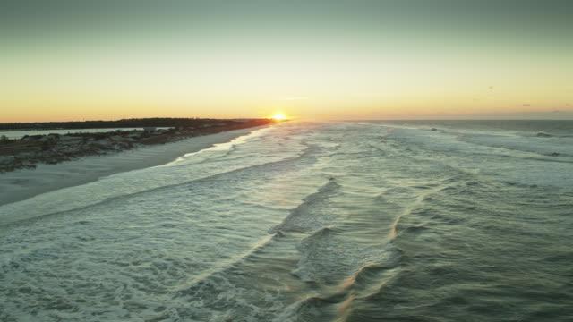Vol au-dessus des vagues de l'océan pendant que le soleil se lève - Vidéo