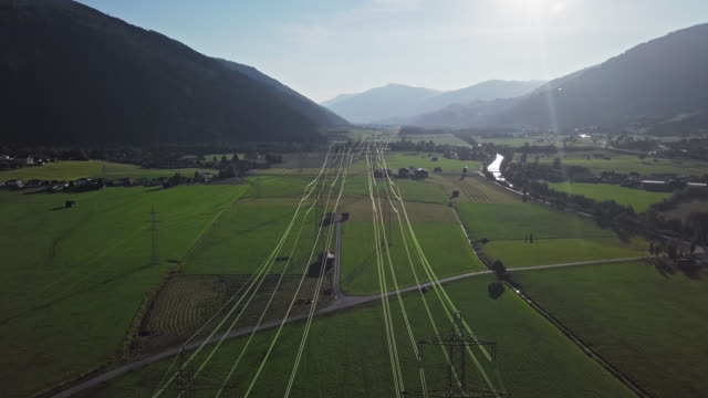Flight over of high voltage power line in mountain valley at sunset.