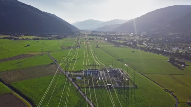 vídeos de stock e filmes b-roll de flight over of high voltage power line in mountain valley at sunset. - fila arranjo