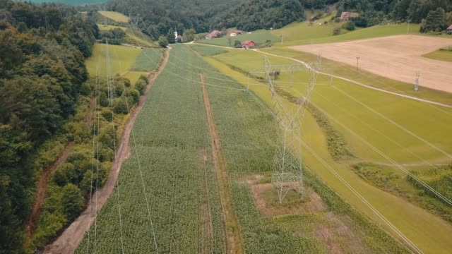 Flight over of high voltage power lines Aerial view of a high voltage power pylon in the middle of forest and agricultural fields. high voltage sign stock videos & royalty-free footage