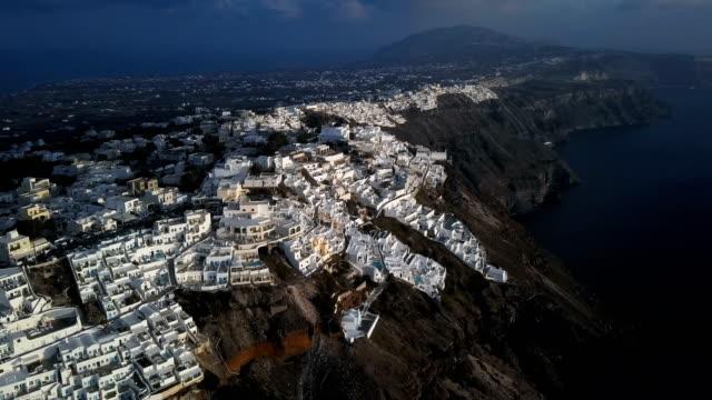 flight over of imerovigli village and skaros rock at sunset, santorini island, greece - morze egejskie filmów i materiałów b-roll