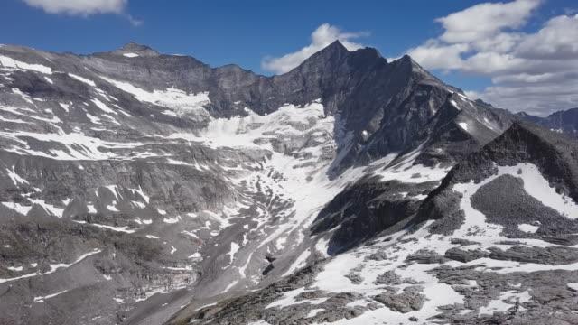 vídeos de stock, filmes e b-roll de voo sobre a geleira odenwinkelkees perto de grossglockner no ensolarado dia de verão, na terra de hohe tauern, salzburger, áustria. - áustria