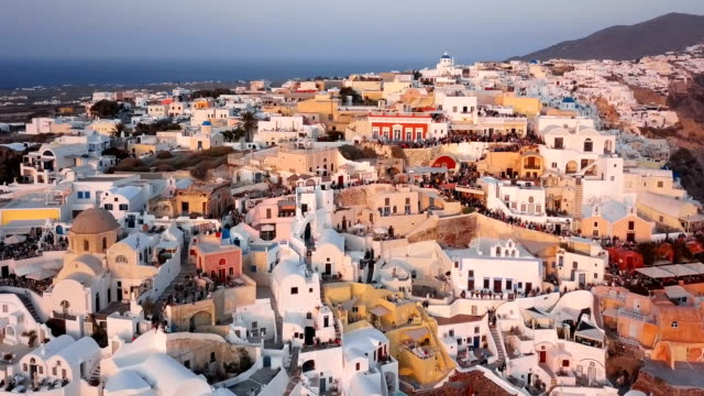 Flight over of Oia town just before sunset, Santorini island, Greece Aerial panorama of Oia town at sunset, Santorini greek islands stock videos & royalty-free footage