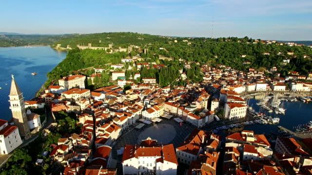 旧市街ピランの上空を飛行し、古い家屋、屋根、聖ジョージ教区教会、タルティーニ広場、要塞と海と空中パノラマビュー。スロベニア。 - スロベニア点の映像素材/bロール
