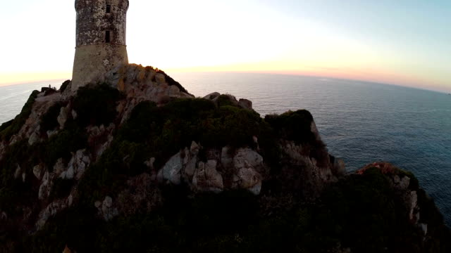 Flight over old tower with background of the sea at sunset. Tour de la Parata, Ajaccio, Corsica, France. Aerial view. video