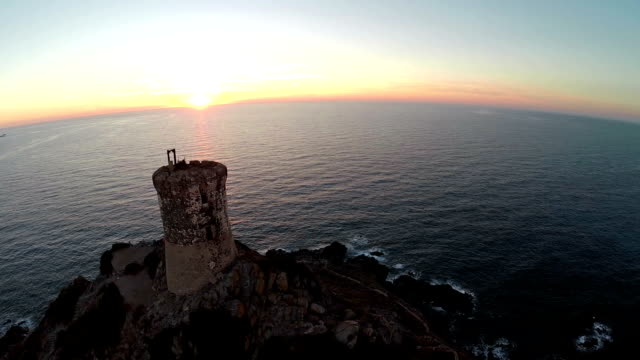 Flight over old tower with background of the sea at sunset. Tour de la Parata, Ajaccio, Corsica, France. Aerial panoramic view. video