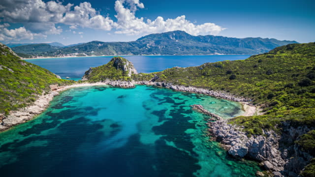 Flight over Porto Timoni beach in Corfu, Greece Aerial shot of Porto Timoni beach in Corfu. Located in the Ionian Sea of Greece the idyllic beach is surround by crystal clear turquoise water. greek islands stock videos & royalty-free footage