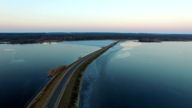 4K. Flight over road in the frozen lake in winter on sunset, aerial view. video
