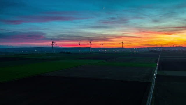 Flight over rural landscape with wind turbines under dramatic sunset sky video