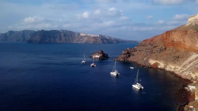 flight over small island church (nisis agios nikolaos) near oia town, santorini island, greece - morze egejskie filmów i materiałów b-roll