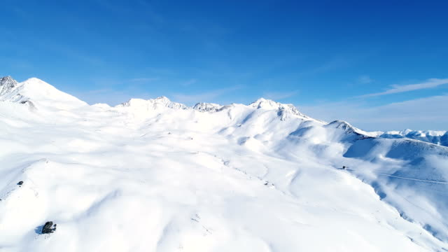 Flight over snowy mountain range with a drone under a blue sky. Mountains peak cover with snow in France. A relaxing white scenery in winter, perfect for extreme sport.