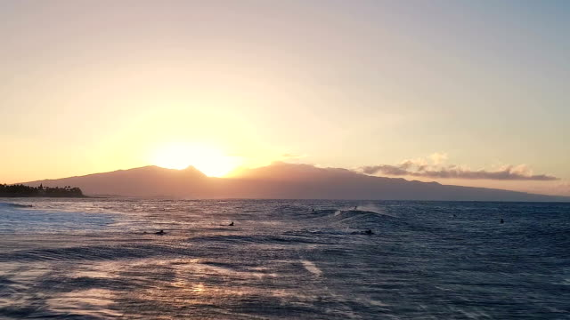 Flight Over Surfers Floating in Ocean Waves at Sunset. Amazing Sunset Aerial Ocean View video