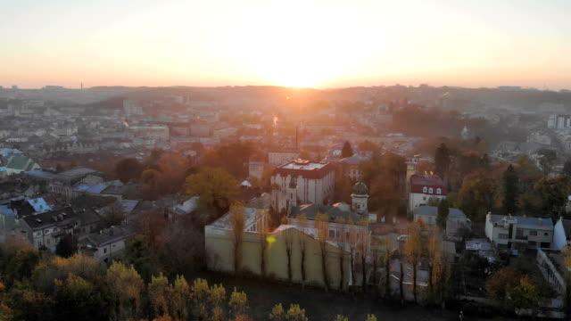 vídeos de stock, filmes e b-roll de voo sobre a parte central da cidade de lviv, na ucrânia. o sol nasce de manhã sobre a cidade. belo panorama da cidade de manhã. os raios do sol brilhar na câmara - sol nascente horizonte drone cidade